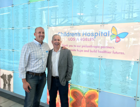 Co-Founders Jeff Kreshek and Andrew Apfelberg standing proudly by the donor wall at CHLA.