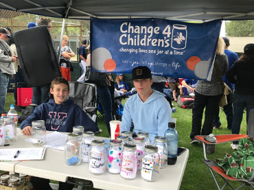 Two boys sit at the Change 4 Children's Booth at Encino Little League