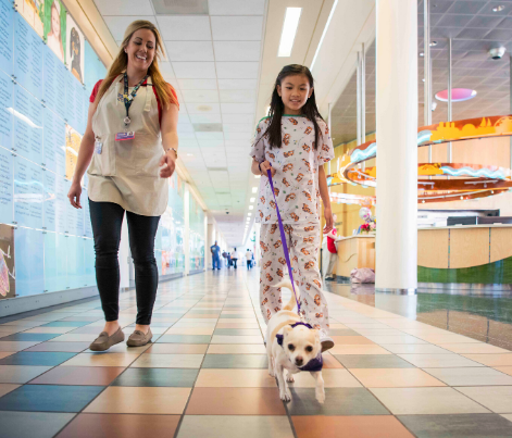 A patient walks with a child life specialist