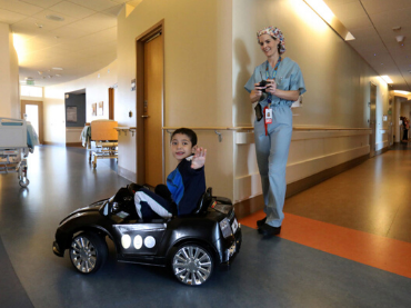 A nurse operates a remote control car with a patient inside.