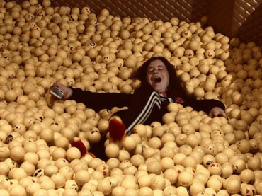 A child happily lays in a ball pit under the individuals heading.