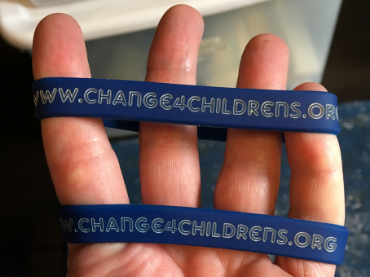 A hand with 2 change 4 children's bracelets are displayed above ways to give.