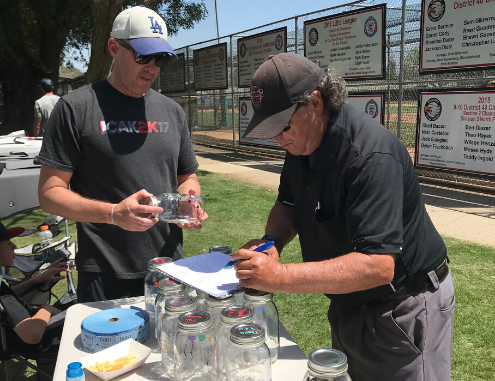Jeff Kreshek stands with an umpire at the Encino Little League Field Table. The ump is checking out a Change 4 Children's jar.